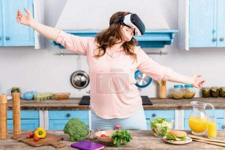 smiling overweight woman in virtual reality headset standing at table with fresh vegetables in kitchen at home