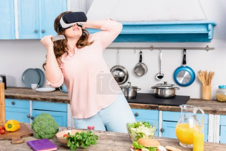 young woman with knife in virtual reality headset standing at table with fresh vegetables in kitchen at home