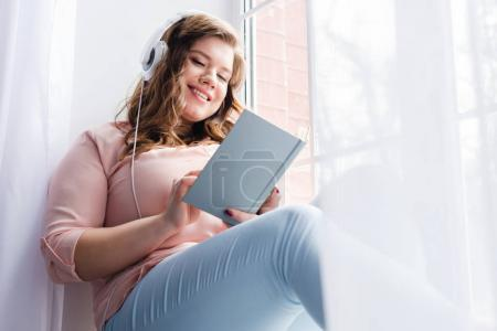 young woman in headphones reading book while sitting on windowsill at home