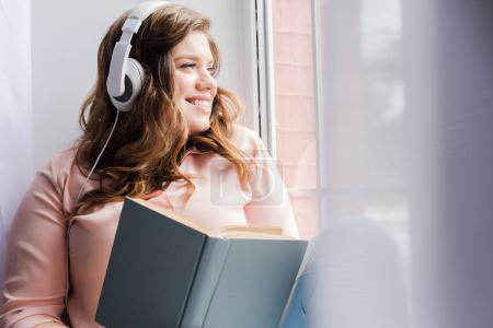 Photo pour Femme souriante dans les écouteurs avec livre assis sur le rebord de la fenêtre à la maison - image libre de droit