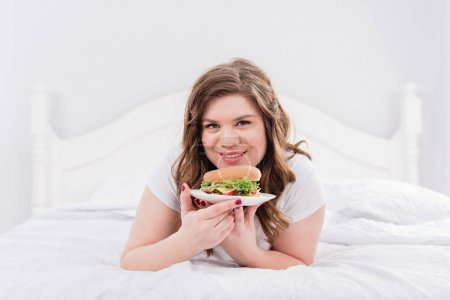 portrait of overweight smiling woman in pajama with burger on bed at home