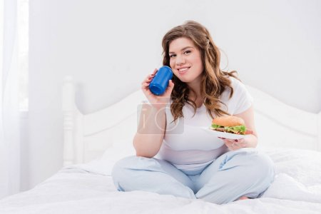 overweight smiling woman in pajama with soda drink and burger on bed at home