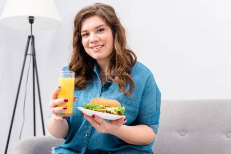 Photo for Overweight smiling woman with glass of juice and burger on plate in hands at home - Royalty Free Image