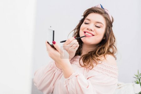 portrait of pretty smiling young woman applying lip gloss while doing makeup at home