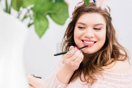 portrait of smiling young woman applying lip gloss while doing makeup at home