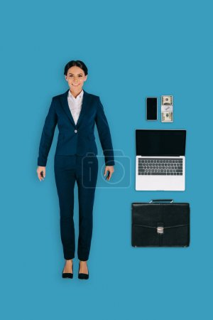 top view of businesswoman with laptop, briefcase, money and smartphone isolated on blue background
