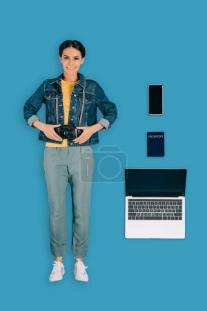 top view of stylish female traveler with photo camera, laptop, smartphone and passport isolated on blue background