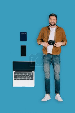 top view of stylish male traveler with photo camera, laptop, smartphone and passport isolated on blue backgronud