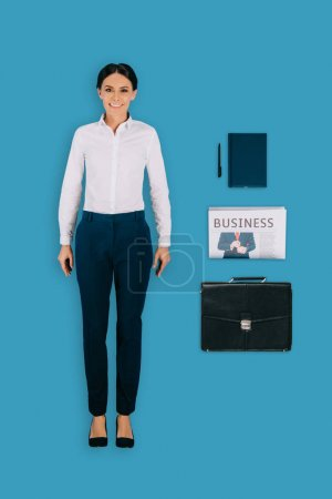top view of businesswoman with briefcase, textbook, pen and newspaper isolated on blue background