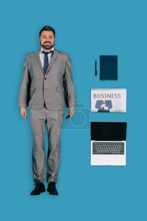 top view of businessman with laptop, newspaper, textbook and pen isolated on blue background