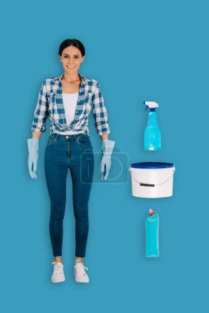 top view of female cleaner in protective gloves with bottle spray, bucket and cleaning fluid isolated on blue background