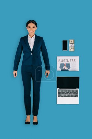 top view of businesswoman with laptop, newspaper, money and smartphone isolated on blue background