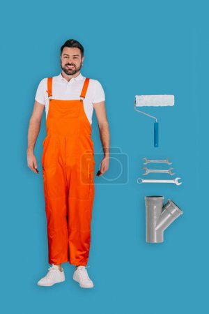 top view of repairman with spanners, paint roller and pipe isolated on blue background