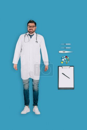 top view of male doctor with stethoscope, pills, clipboard, syringes, thermometer isolated on blue background