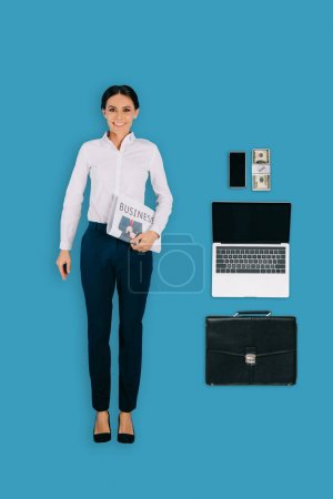 top view of businesswoman with newspaper, briefcase, laptop, smartphone and money isolated on blue background