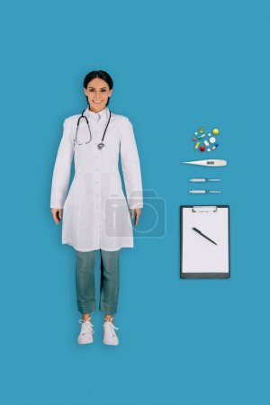 top view of female doctor with clipboard, pen, thermometer, pills and syringes isolated on blue background
