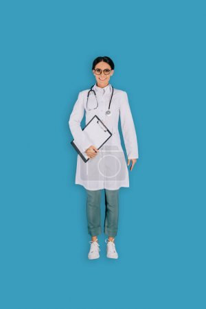 top view of female doctor with stethoscope and clipboard isolated on blue background