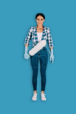 top view of female cleaner in protective gloves with duster isolated on blue background