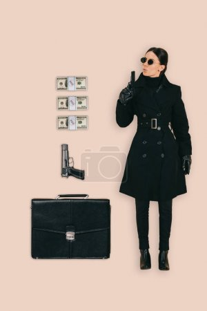 top view of female killer in sunglasses with briefcase, handguns and cash isolated on pink background