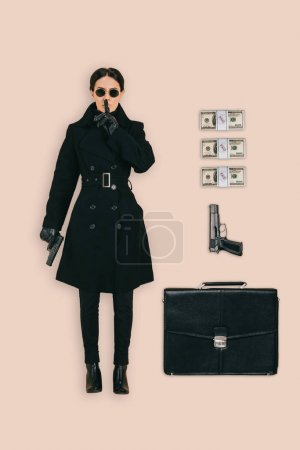 top view of female killer in sunglasses doing shushing gesture with briefcase, handguns and cash isolated on pink background