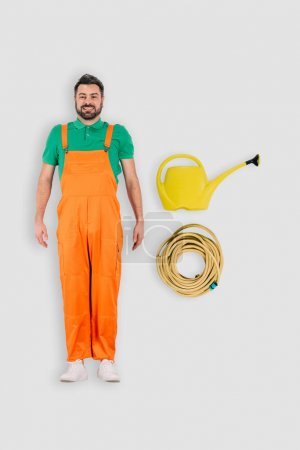 top view of male gardener with watering can and hose isolated on white background