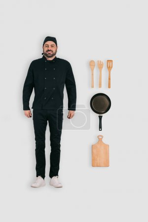 top view of male chef with frying pan, cutting board and spatulas isolated on white background