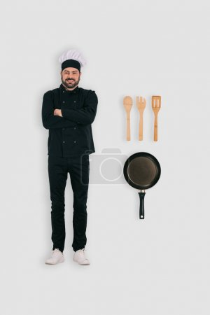 top view of male chef with frying pan and spatulas isolated on white background
