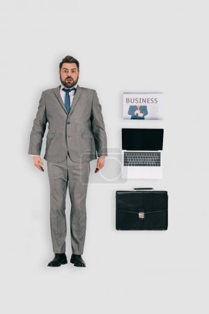 top view of businessman with newspaper, laptop and briefcase isolated on white background