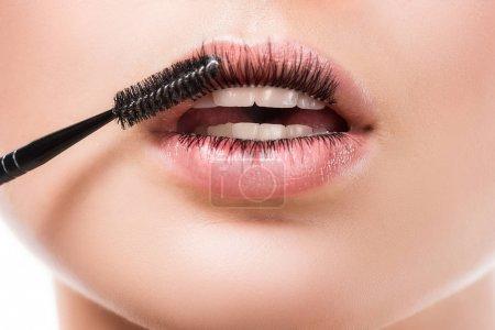 cropped image of woman applying mascara on eyelashes on lips isolated on white