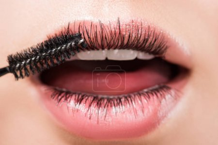 cropped image of woman applying black mascara on eyelashes in mouth isolated on white