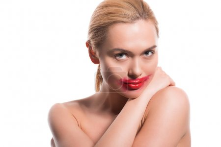 cheerful beautiful woman with smeared red lipstick on face looking at camera isolated on white