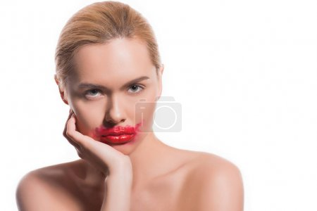 beautiful woman with smeared red lipstick on face isolated on white