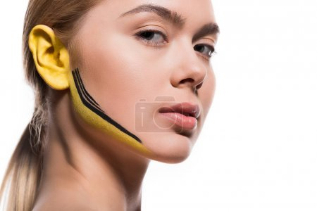 beautiful woman with yellow and black paints on ear and face isolated on white