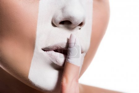 cropped image of woman with white paint on face showing silence sign isolated on white