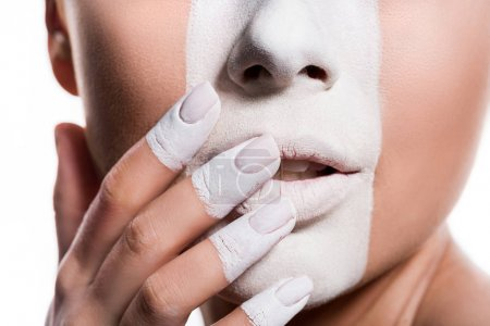 cropped image of woman with white paint on face and fingers touching lips isolated on white