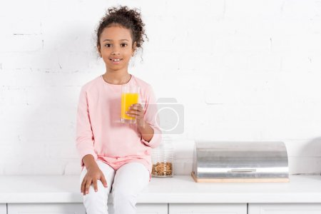 african american kid with glass of orange juice sitting in kitchen and looking at camera