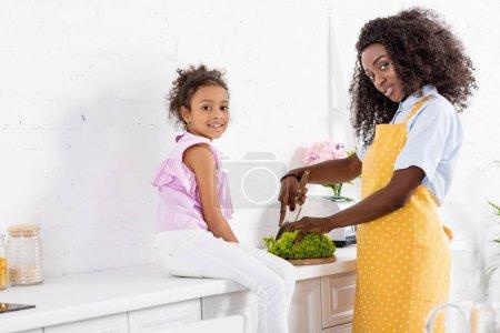Photo pour Afro-américain homme et fille coupe laitue sur cuisine - image libre de droit