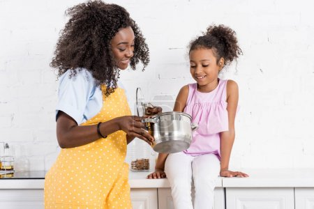 happy african american mother and daughter cooking on kitchen together