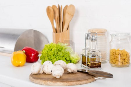 bell peppers, lettuce and mushrooms on wooden board and oil in kitchen