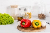 bell pepper, mushrooms and lettuce on wooden board in kitchen with jars
