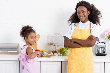african american mother with crossed arms and daughter cutting vegetables on kitchen