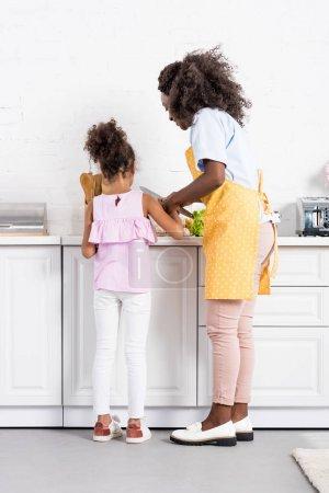 Photo pour Afro-américaine mère et fille couper des légumes sur la cuisine ensemble - image libre de droit