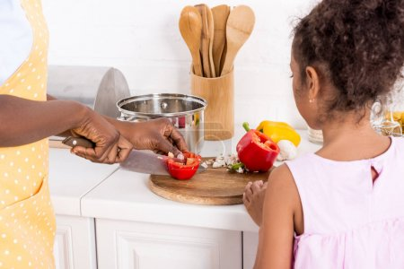 cropped view of african american mother and daughter cutting bell pepper on kitchen