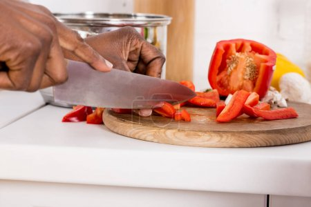cropped view of african american woman cutting red bell pepper on wooden board on kitchen