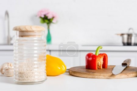 rice in glass jar and bell peppers on wooden board with knife