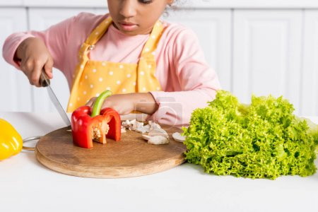 Photo for Cropped view of african american kid in apron cutting vegetables on wooden board in kitchen - Royalty Free Image