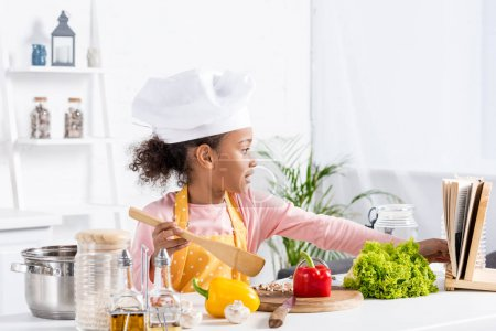adorable african american child in apron and chef hat cooking on kitchen