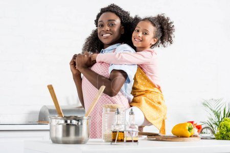 Foto de Feliz madre afroamericana piggybacking hija en la cocina - Imagen libre de derechos