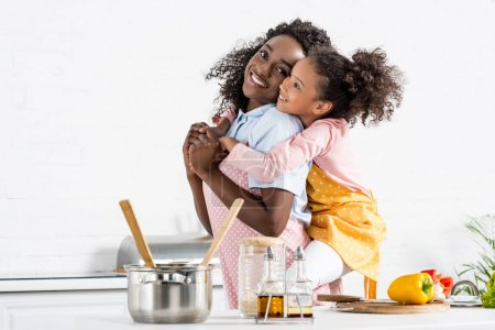 african american mother piggybacking daughter in apron on kitchen