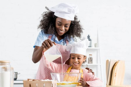 african american mother and daughter in chef hats pouring milk in bowl with ingredientes for dough